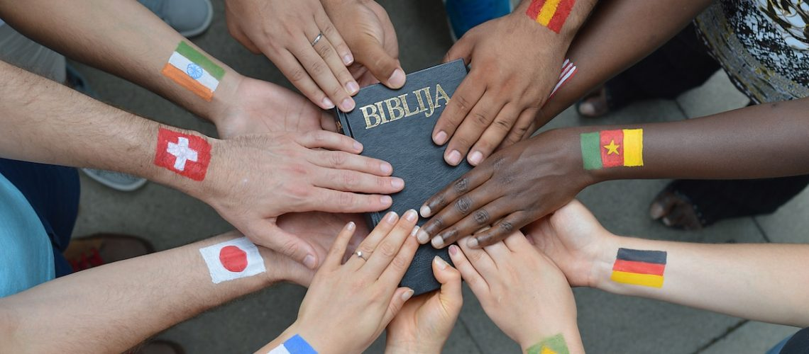 International brothers and sisters in Christ holding a bible together.
